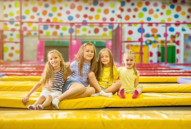 Маленькие белокурые улыбающиеся девушки сидят вместе на желтом батуте