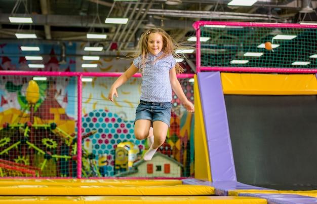 Маленькая девочка прыгает на батуте в парке развлечений