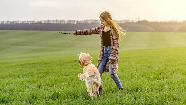 Девушка играет с ретривером в природе