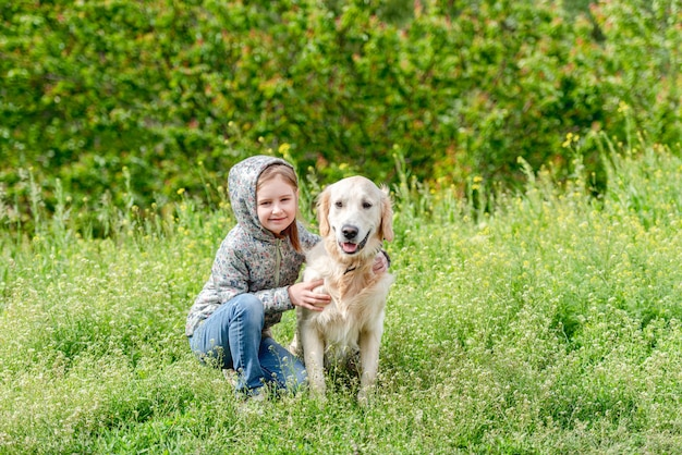 Счастливая маленькая девочка обнимает милый пес