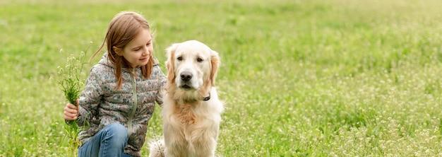 Улыбающаяся маленькая девочка смотрит на милую собаку