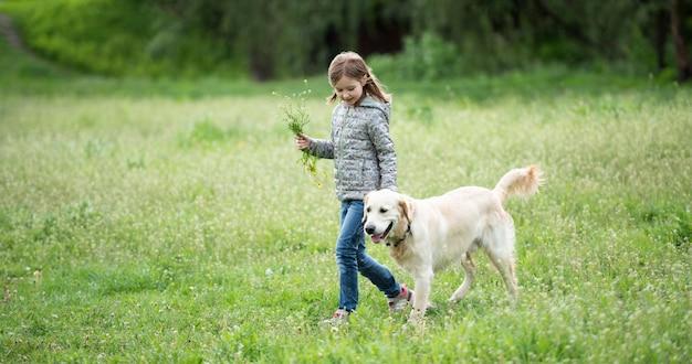 Милая маленькая девочка с цветами гуляет с собакой