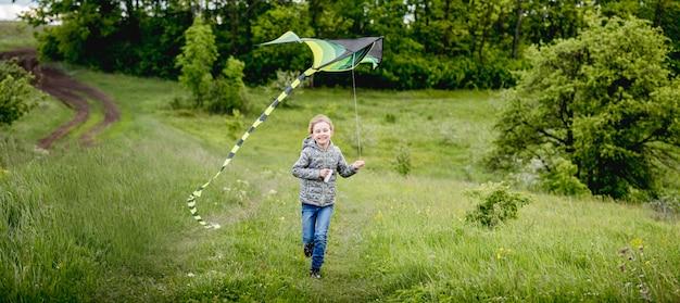 Счастливая маленькая девочка летает яркий кайт