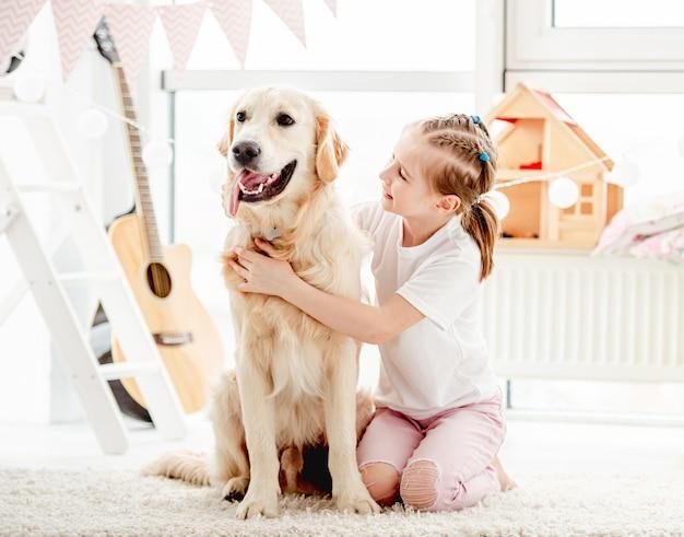 Счастливый маленькая девочка обнимаются красивая собака