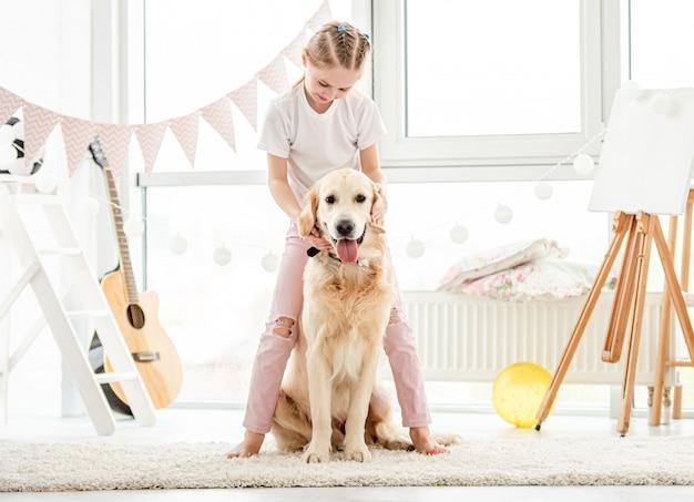 Милая маленькая девочка, играя с собакой