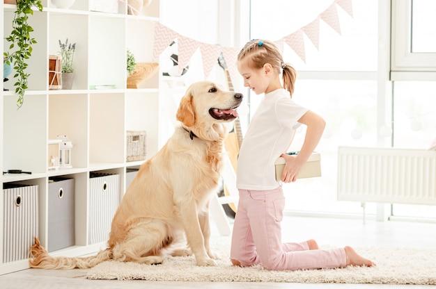 Маленькая девочка вручает подарок собаке