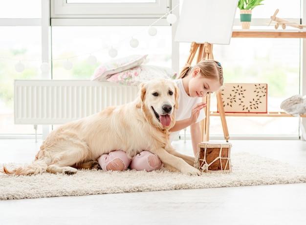 Маленькая девочка играет музыку с собакой