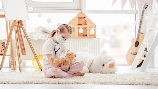 Маленькая девочка слушает по фонендоскопу
