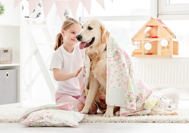 Красивая маленькая девочка покрывая милую собаку