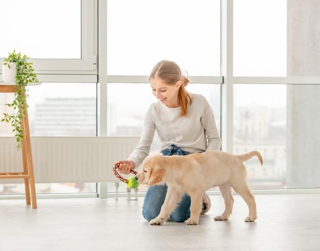 Девушка играет с молодой собакой