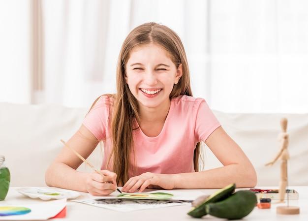 緑のアボカドを描くと笑顔の女の子