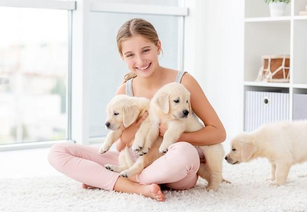 レトリーバーの子犬のグループを抱き締める女の子