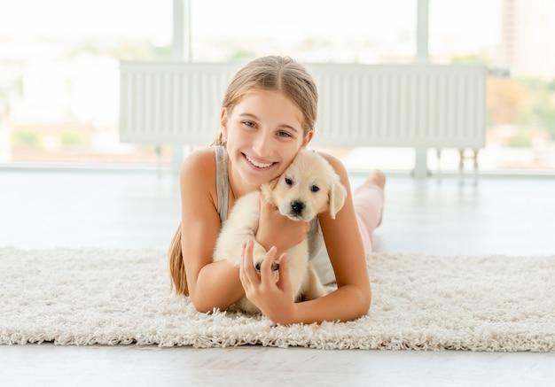 レトリーバーの子犬を抱きしめる女の子