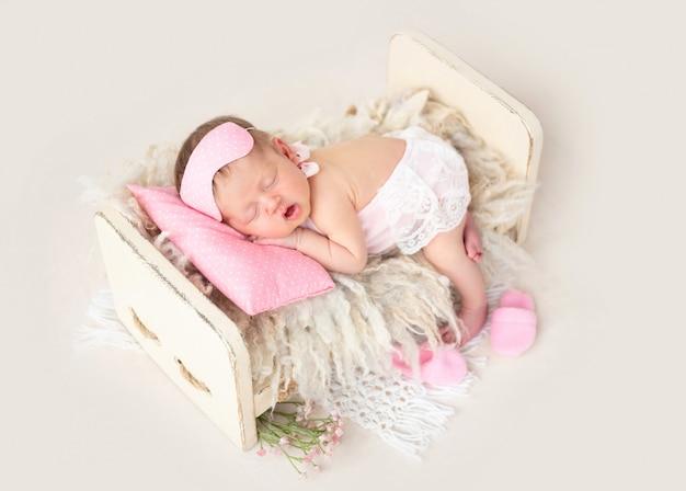 小さなベッドで寝ている新生児