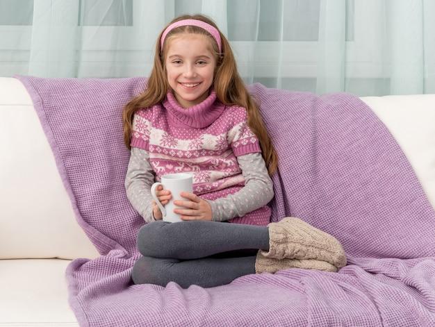 暖かい毛布が付いているソファーに素敵な女の子