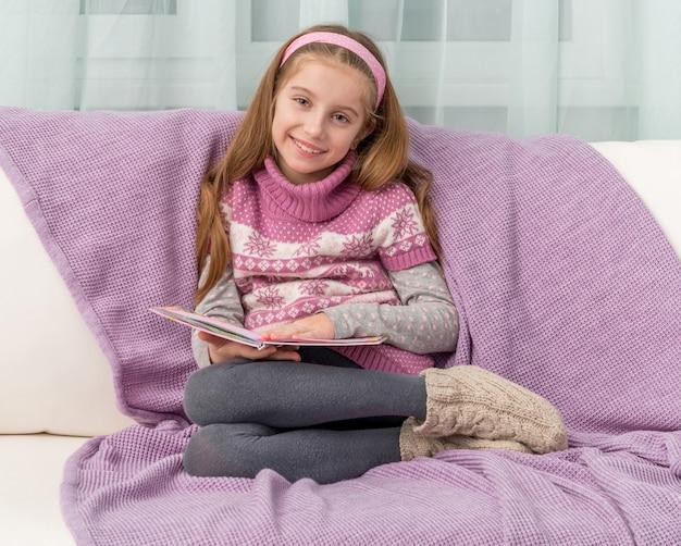 本が付いているソファーの上の少女