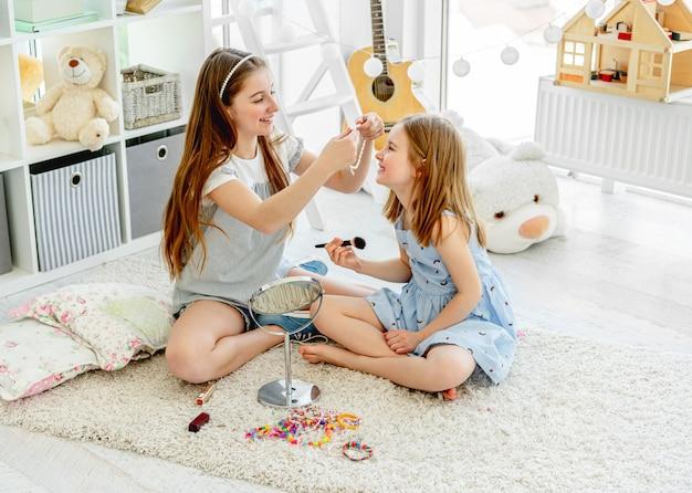 メイクで遊ぶ陽気な女の子子供