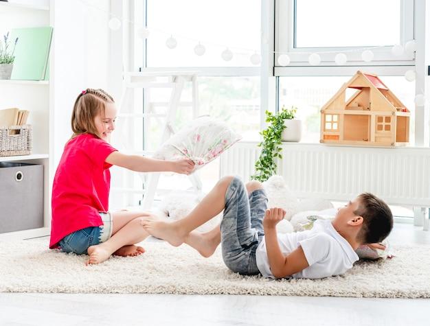枕を戦う幸せな小さな友達
