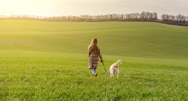 緑の野原で犬の散歩の女の子