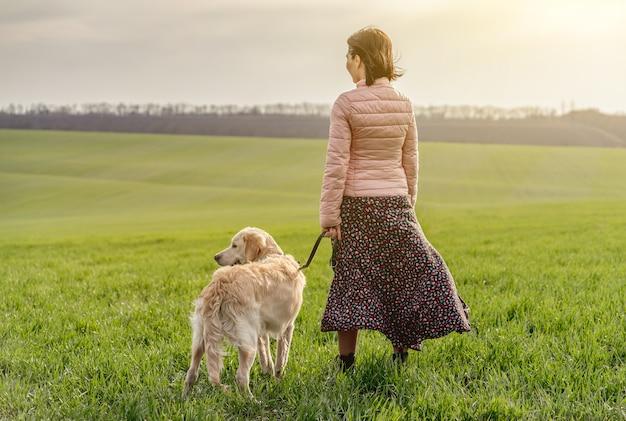 緑の芝生の上に犬を持つ女性