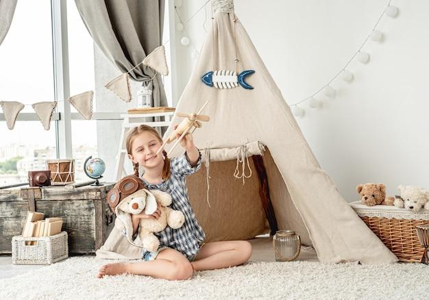 木製の飛行機を飛んで幸せな女の子