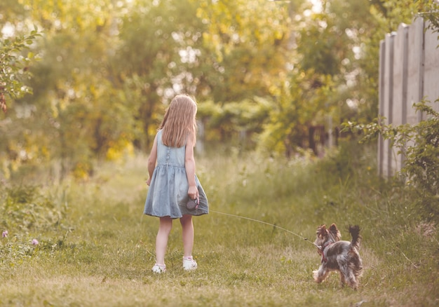 Маленькая девочка с собакой в сельской местности