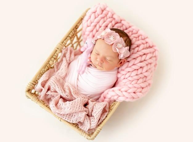 Новорожденный ребенок спит в корзине