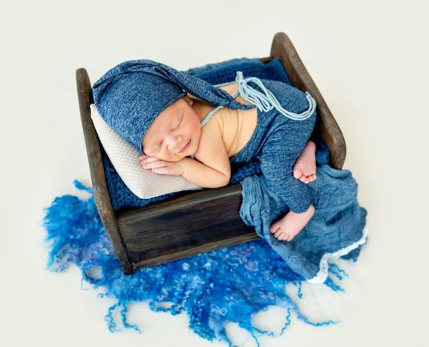 眠っている青いボンネットでかわいい男の子