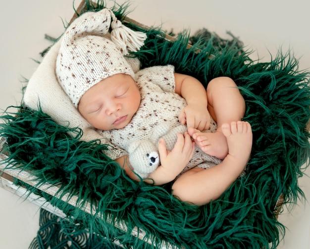 Мечтательный новорожденный ребенок спит на кровати