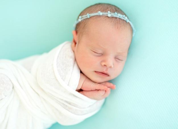 Спящий новорожденный в синем оголовье