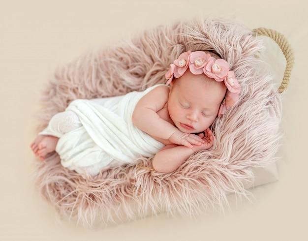 Милая новорожденная девушка спит в детской корзине