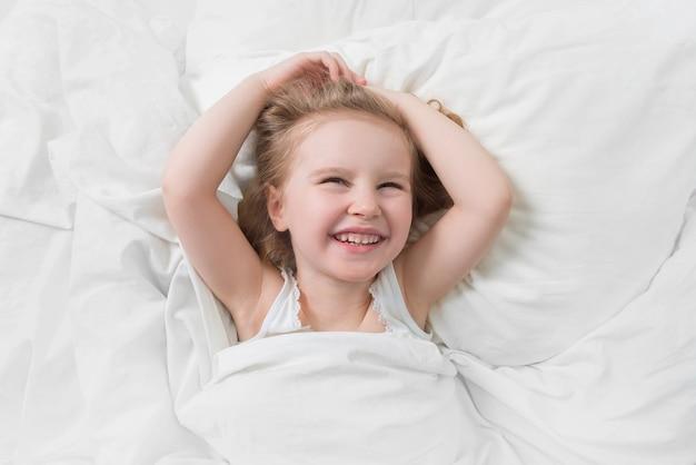 ベッドで笑顔の娘の素敵な感情