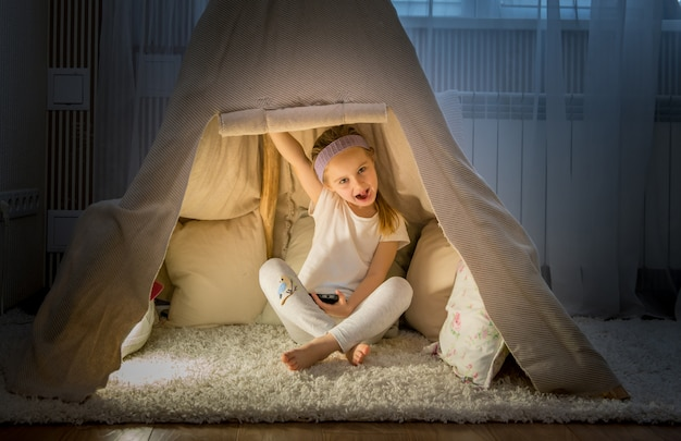 Маленькая девочка в палатке типи в комнате