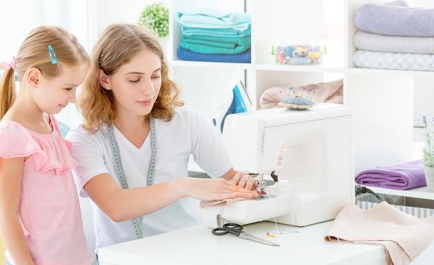 Маленькая девочка учится шить
