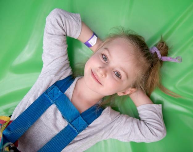 緑のジムのマットの上に敷設する少女
