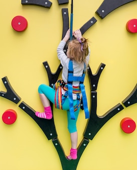 Маленькая девочка в страховых поездах на стене для скалолазания