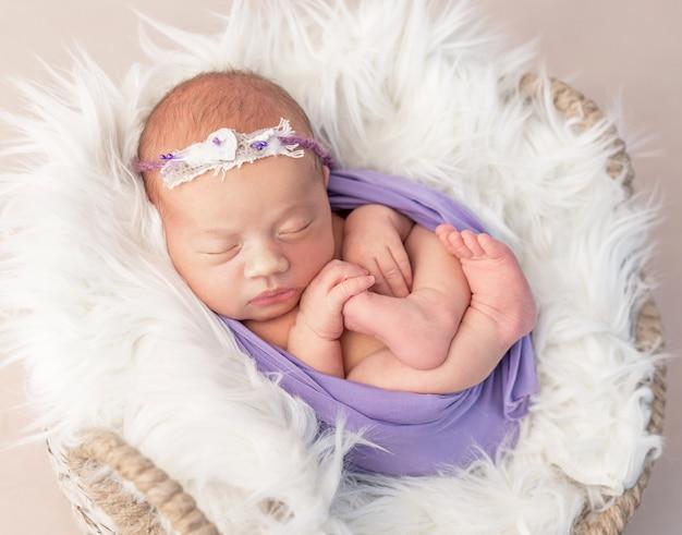 おもちゃで羊毛で覆われたバスケットで生まれたばかりの子供