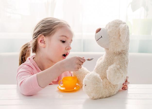 おもちゃのテディベアを餌かわいい女の子