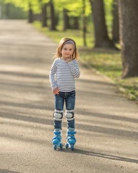 ヘルメットと路地でスケートを持つ少女