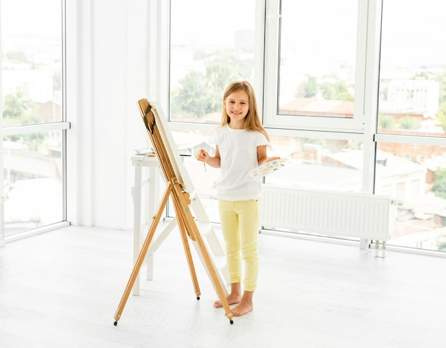 屋内で美しい風景を描く少女