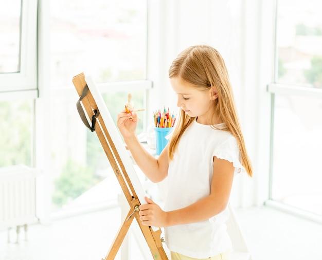Малышка рисует разные картины на мольберте
