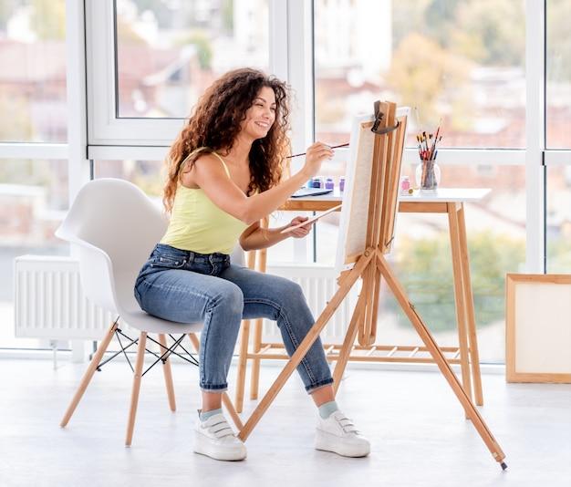 Улыбающийся художник рисует на мольберте