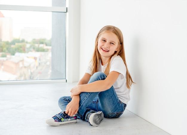 Улыбающаяся маленькая девочка сидит на полу