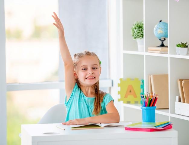 Красивая маленькая девочка подняла руку в классе