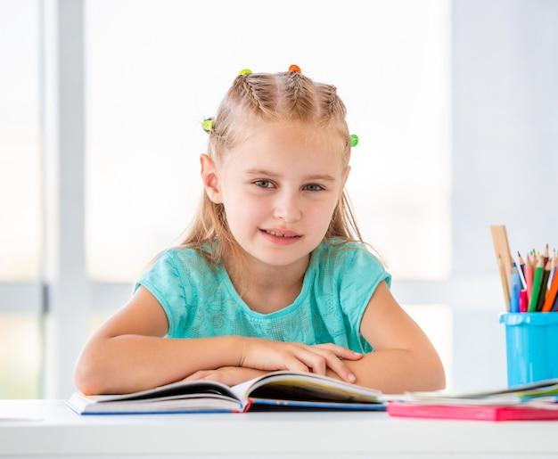 開いた本に座っているかわいい女子高生