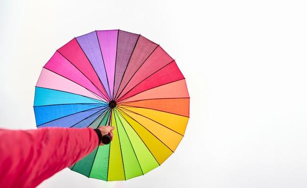 白い空に色とりどりの傘を持っている手