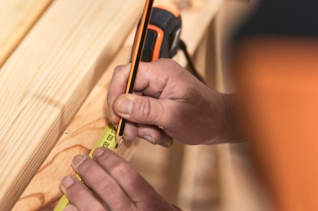 Руки плотника проводят замеры на дереве с помощью метра и карандаша. ремонт, строительство и концепция дома