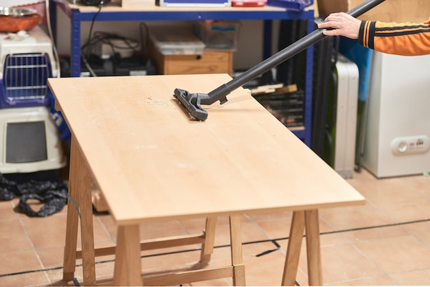 おがくずと木材の残骸で作業テーブル上を掃除機で掃除する若い男の手の詳細