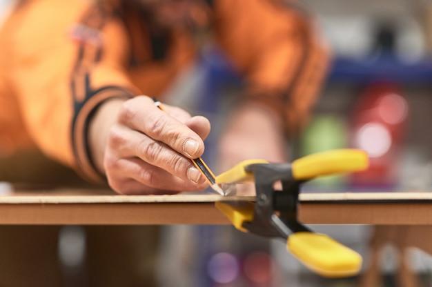 非常に浅い被写界深度を持つ鉛筆で木材をマーキングする指の詳細
