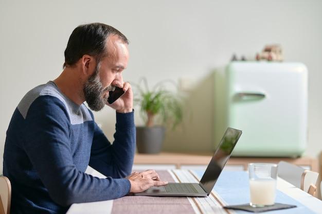 彼のラップトップに取り組んでいる間彼のスマートフォンで話している若いひげを生やした男の側面図